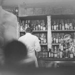 A monochrome scene at a busy restaurant bar.