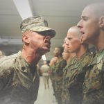 A drill sergeant yells at a hapless recruit in a line-up of troops.